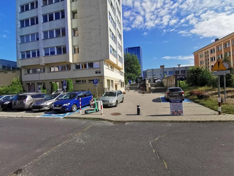 Zdjęcie przedstawia parking z samochodami przy biurowcu, w którym znajduje się Inspektorat, na którym widać dwa oznaczone miejsca do parkowania dla osób z niepełnosprawnościami