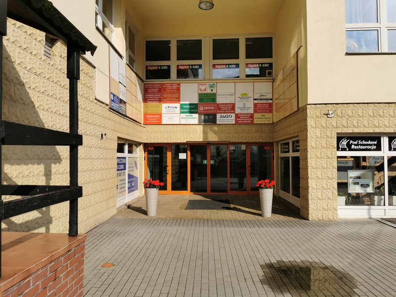 Zdjęcie przedstawia główne wejście do biurowca, w którym siedzibę ma inspektorat. Na zdjęciu widzimy przeszklone, automatycznie rozsuwane drzwi a nad nimi tablice informacyjne instytucji, które mieszczą się w biurowcu.