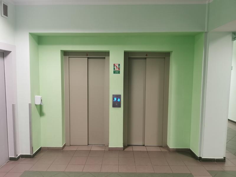 Zdjęcie przedstawia hol biurowca oraz drzwi dwóch wind dostosowanych dla osób ze specjalnymi potrzebami na tle zielonej ściany