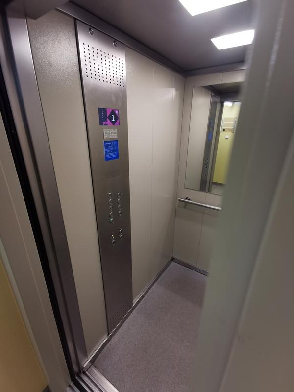 Zdjęcie przedstawia wnętrze windy dostosowanej dla osób ze specjalnymi potrzebami, która funkcjonuje w biurowcu.