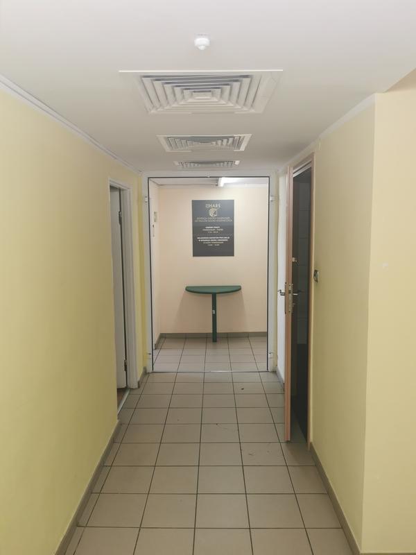 Zdjęcie przedstawia korytarz prowadzący do sekretariatu Inspektoratu z wind. Na ścianie widzimy zieloną tablicę informacyjną Inspektoratu.