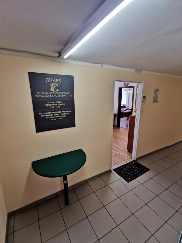 Zdjęcie przedstawia wejście do sekretariatu Inspektoratu. Na ścianie widzimy zieloną tablicę informacyjną oraz otwarte drzwi.