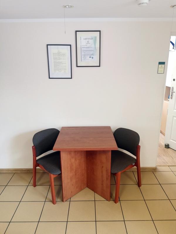 Zdjęcie przedstawia miejsce przyjmowania interesantów w Inspektoracie. Na zdjęciu widzimy stół z dwoma fotelami postawione przy ścianie.